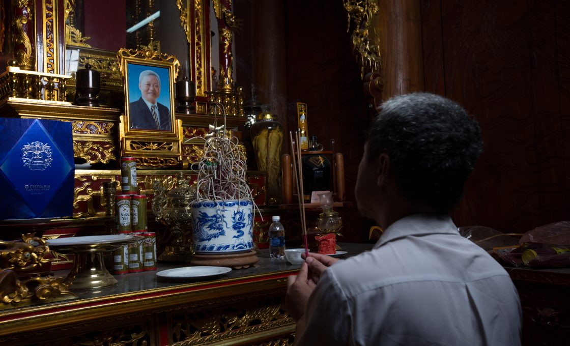 Dung lights up an incense in front of his father's altar.